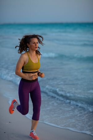 Full length portrait of fit woman in sport clothes on the beach at sunset jogging. 版權商用圖片