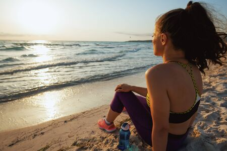 Seen from behind active woman in sport clothes with bottle of water sitting and relaxing after workout on the seashore in the evening.