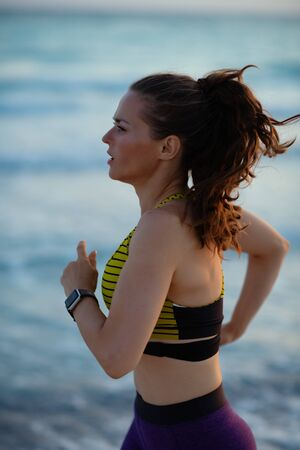 active sports woman in sport clothes on the seacoast in the evening jogging. Imagens