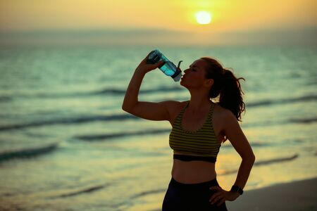 Silhouette of fit woman in sport style clothes on the beach at sunset drinking water from bottle.