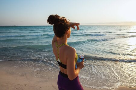 Seen from behind healthy sports woman in fitness clothes with bottle of water looking into the distance on the seashore in the evening. 版權商用圖片