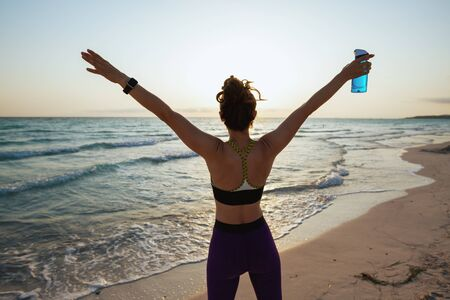 Seen from behind fit sports woman in sport style clothes with bottle of water rejoicing on the ocean coast at sunset.
