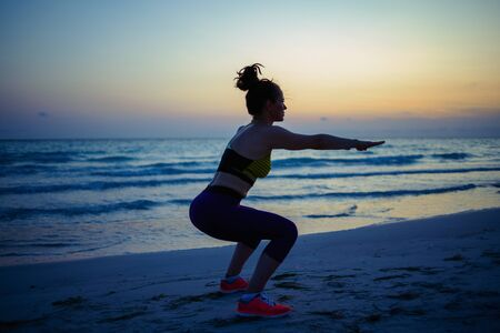 Silhouette of fitness sports woman in fitness clothes on the beach in the evening doing squats. Imagens