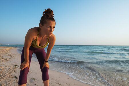 fitness sports woman in sport clothes on the ocean coast in the evening catching breath after exercise. 版權商用圖片