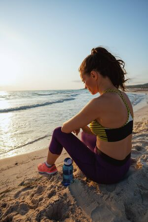 Seen from behind young sports woman in sport clothes with bottle of water relaxing after workout on the beach at sunset.
