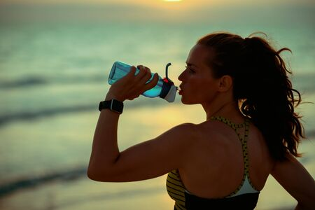 Silhouette of young sports woman in sport style clothes on the ocean shore at sunset drinking water from bottle.