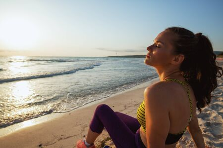 healthy woman in sport style clothes on the ocean coast in the evening relaxing after workout. Stock Photo
