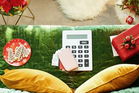 Holiday season. Upper view of purse with money and credit cards and white calculator on sofa in the modern living room at Christmas.