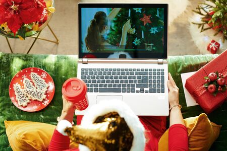 Holiday season. Upper view of modern woman in sparkle gold sequin santa hat sitting on divan in the modern living room at Christmas using internet tv on a laptop.