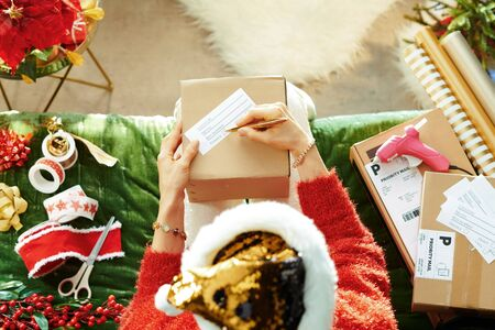 Holiday season. Upper view of stylish woman in sparkle gold sequin santa hat sitting on sofa in the modern living room at Christmas sending parcels.