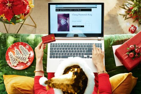 Holiday season. Upper view of elegant female in sparkle gold sequin santa hat with credit card ordering in jewellery online shop while sitting on divan in the modern living room at Christmas.