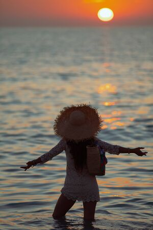 Silhouette of elegant 40 year old woman in white dress with open arms rejoicing while standing in the ocean on the seacoast at sunset. 스톡 콘텐츠