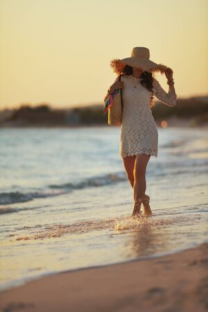 Full length portrait of trendy middle age woman in white dress and straw hat on the seacoast at sunset having fun time. 스톡 콘텐츠