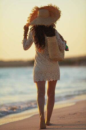 Full length portrait of young woman in white dress and straw hat on the seacoast at sunset walking. 스톡 콘텐츠