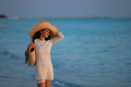 relaxed modern middle age woman in white dress and straw hat standing on the beach at sunset.