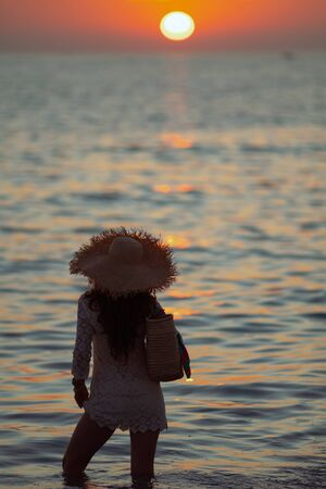 Silhouette of stylish woman in white dress on the ocean shore at sunset standing in the sea.