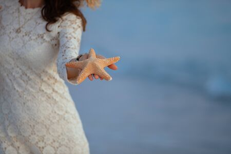 Closeup on woman in white dress on the seashore at sunset showing starfish.