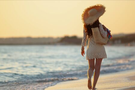 Full length portrait of trendy middle age woman in white dress and straw hat on the ocean coast at sunset walking.