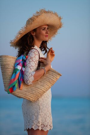 pensive modern middle age woman in white dress and straw hat on the ocean coast at sunset looking into the distance.