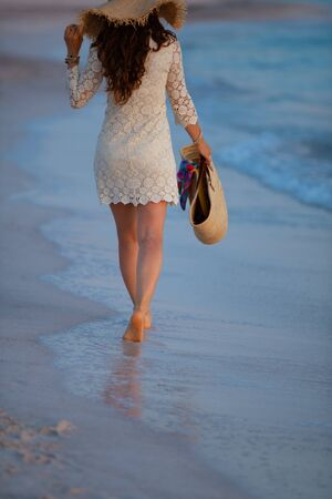 Seen from behind modern 40 year old woman in white dress and straw hat on the beach at sunset walking.