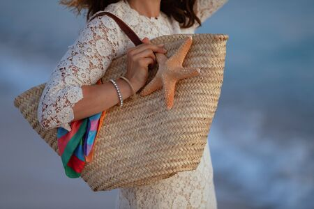 Closeup on stylish woman in white dress on the seashore at sunset holding beach straw bag and starfish.