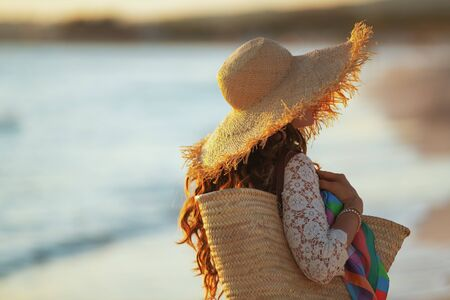 Seen from behind young woman in white dress and straw hat on the beach at sunset walking. Stock Photo - 133517213