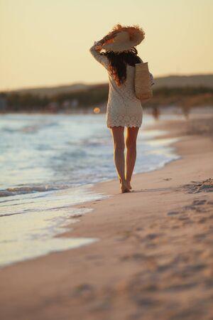 Full length portrait of 40 year old woman in white dress and straw hat on the beach at sunset walking. 스톡 콘텐츠