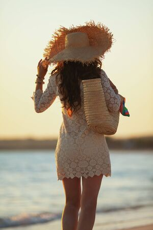 Seen from behind modern middle age woman in white dress and straw hat on the seashore at sunset walking.
