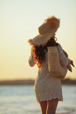 Seen from behind modern woman in white dress and straw hat on the ocean coast at sunset walking.