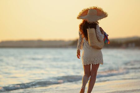 Seen from behind elegant middle age woman in white dress and straw hat on the beach at sunset walking.