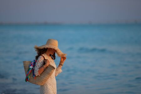 trendy middle age woman in white dress and straw hat standing on the ocean coast at sunset. 스톡 콘텐츠
