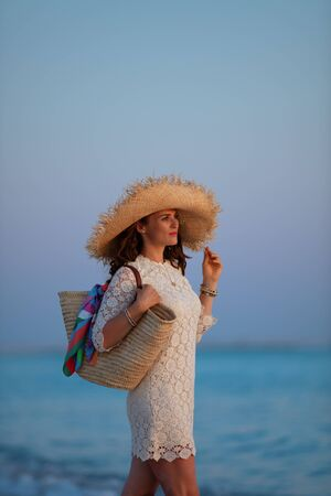 relaxed elegant 40 year old woman in white dress and straw hat on the beach at sunset.