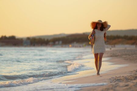 Full length portrait of stylish 40 year old woman in white dress and straw hat on the seacoast at sunset walking.
