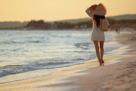 Full length portrait of stylish woman in white dress and straw hat on the seacoast at sunset walking.