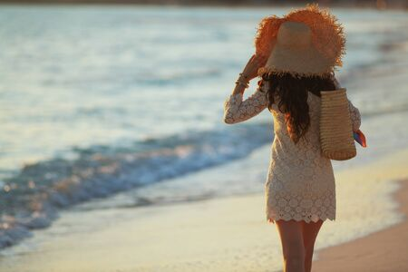 Seen from behind elegant middle age woman in white dress and straw hat on the seashore at sunset walking.