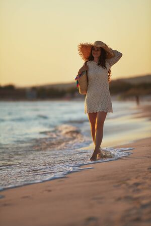 Full length portrait of happy middle age woman in white dress and straw hat on the seashore at sunset enjoying stress free time.