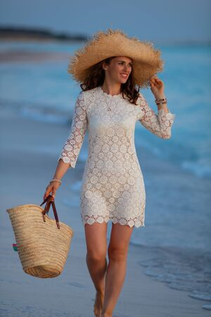 happy stylish middle age woman in white dress and straw hat on the ocean coast at sunset looking into the distance and walking. Stock Photo
