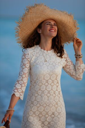 smiling young woman in white dress and straw hat on the ocean coast at sunset enjoying stress free time.