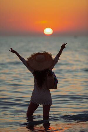 Silhouette of modern woman in white dress on the beach at sunset standing in the sea and rejoicing. 스톡 콘텐츠