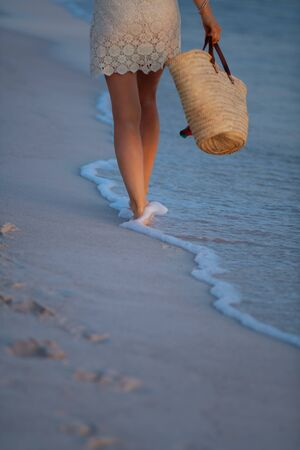 Closeup on elegant 40 year old woman in white dress and straw hat on the beach at sunset walking.