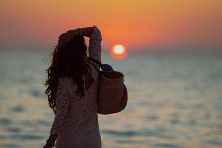 Silhouette of 40 year old woman in white dress on the ocean coast enjoy sunset. 스톡 콘텐츠