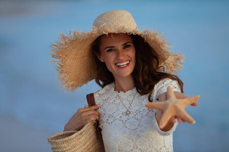 Portrait of happy elegant 40 year old woman in white dress and straw hat on the ocean coast at sunset showing starfish.