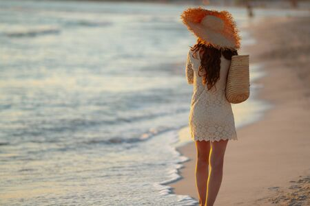 Seen from behind stylish woman in white dress and straw hat on the seashore at sunset walking.