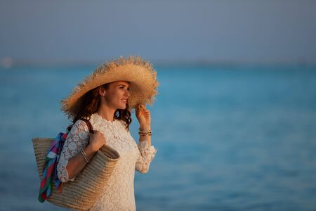 Side view of smiling young woman in white dress and straw hat on the ocean shore at sunset looking into the distance.