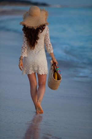 Seen from behind 40 year old woman in white dress and straw hat on the seashore at sunset walking. Stock Photo - 133517282