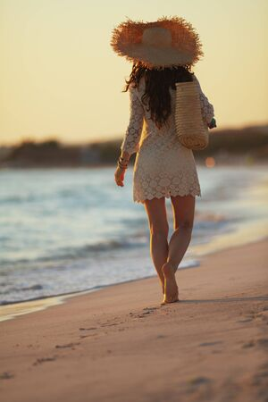 Full length portrait of modern middle age woman in white dress and straw hat on the seashore at sunset walking. 스톡 콘텐츠