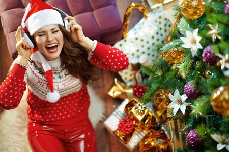 Smiling stylish woman with long brunette hair wearing red white Christmas sweater and elf santa hat listening to the music with headphones under decorated Christmas tree near present boxes.