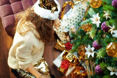 Upper view of stressed trendy 40 year old woman with long brunette hair in gold sequin skirt and white sweater under decorated Christmas tree near present boxes sitting on floor.