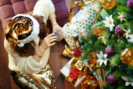 Stressed elegant housewife with long brunette hair in gold sequin skirt and white sweater dripping valerian in a glass with water under decorated Christmas tree near present boxes. Reklamní fotografie