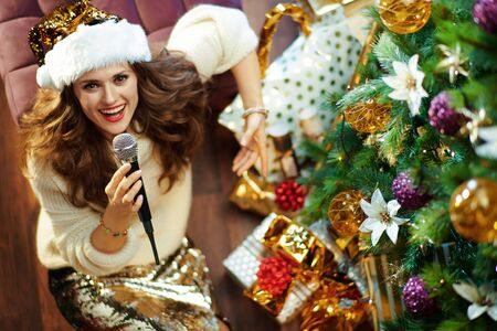 Upper view of smiling elegant 40 year old woman with long brunette hair in gold sequin skirt and white sweater under decorated Christmas tree near present boxes singing into microphone. Stock Photo